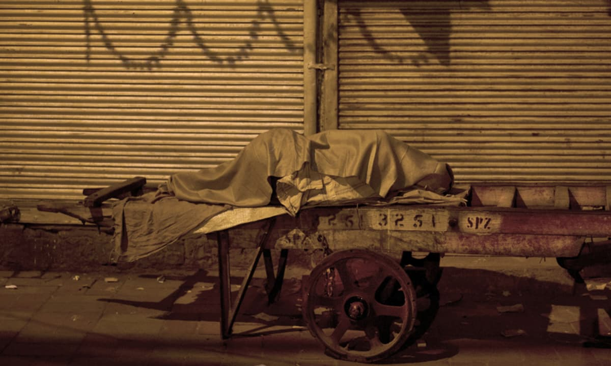 A cart puller sleeps at Khari Baoli, a wholesale spice market, in New Delhi, India. Of the thousands of migrant workers from across India that come to Delhi in search of jobs, many end up pulling or assisting the carts that are widely used to transport goods at Khari Baoli.— AP