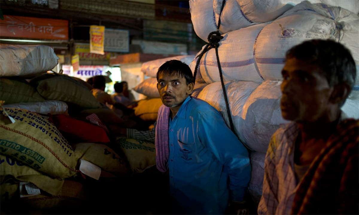 A cart puller looks out after pulling carts throughout the day at khari Baoli spice market in New Delhi, India. The cart pullers take goods from trucks to warehouses, from warehouses to stores, and from one store to another.— AP