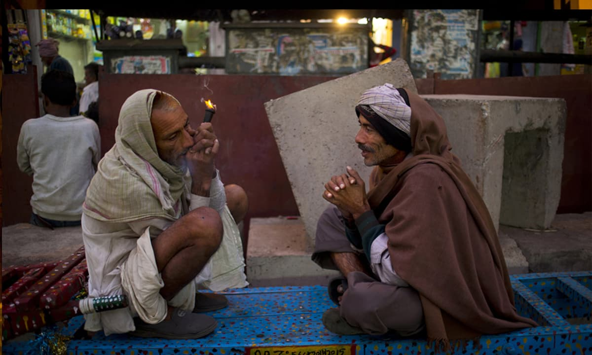 Two cart pullers talk and smoke marijuana in New Delhi, India. With little time for themselves, the cart pullers relax with liquor and an occasional drag of marijuana. (AP Photo/Saurabh Das) — AP