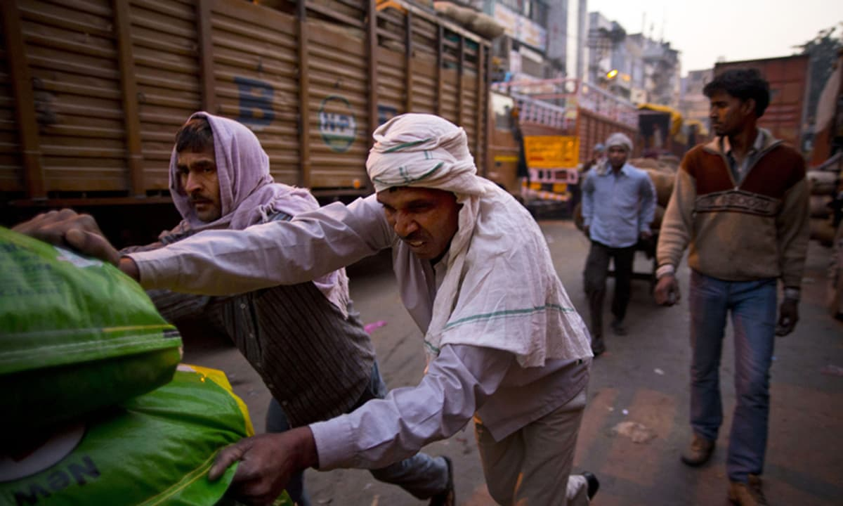 Assistants push a cart in New Delhi, India. Assistants can make as low as seventy cents a day. — AP