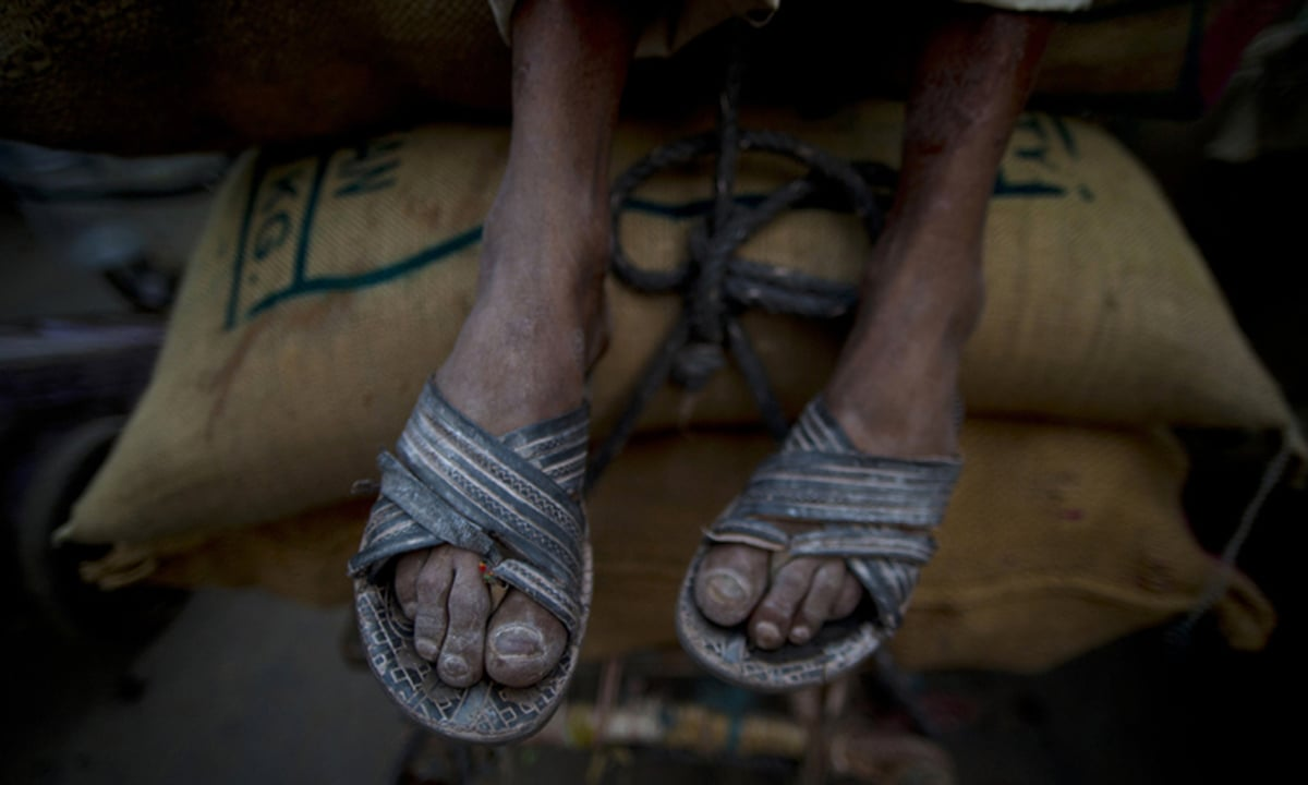 A cart puller hangs his legs covered with dirt and flour as he rests on his loaded cart in New Delhi, India.  Sometimes, cart pullers can pull their carts for as many as 25 kilometers (15 miles) a day.— AP