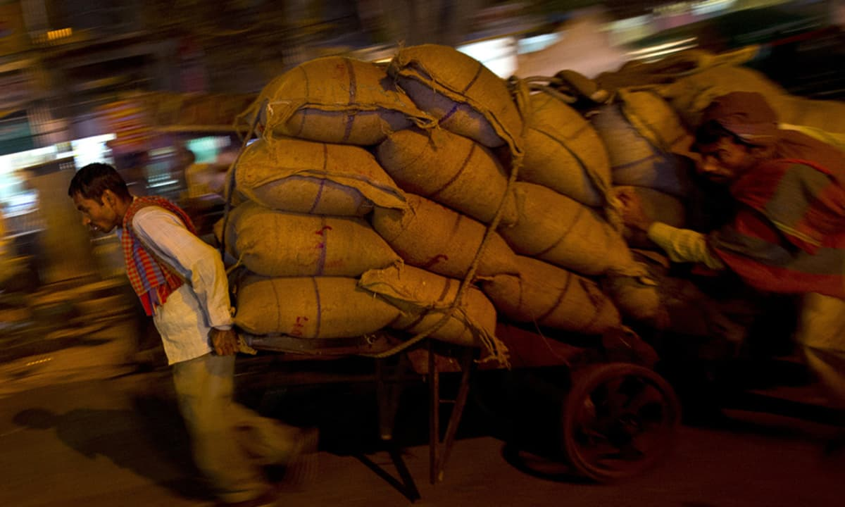 A cart puller transports a load of goods as he is helped by an assistant at the wholesale spice market in New Delhi, India. Cart pullers steer thousands of tons of spices and other dried food every day throughout the market.— AP