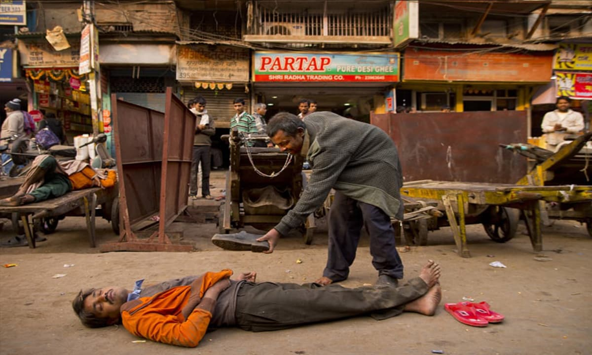 A drunk man offers his shoes to his colleague who passed out after consuming alcohol in New Delhi, India.— AP