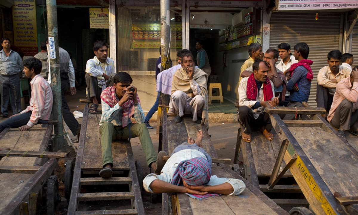 Cart pullers and helpers rest idle on carts after shop owners called for a sudden strike after a theft at the spice market in New Delhi, India. The amount a cart puller earns varies on the amount of loads he carries, their weight and his distance driven. (AP Photo/Saurabh Das)— AP