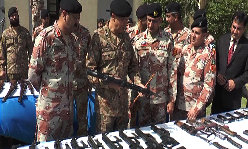 Corps Commander Karachi Lieutenant General Naveed Mukhtar inspecting seized weapons. — DawnNews screengrab