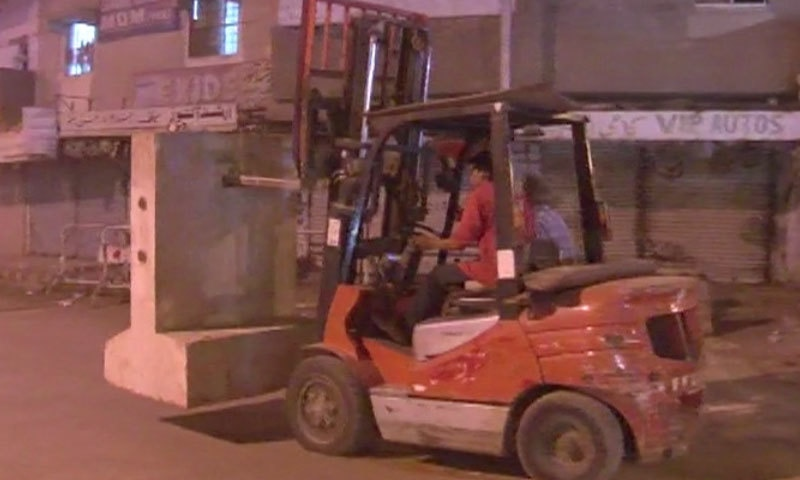 DawnNews screengrab shows a lifter removing barriers outside Nine Zero.