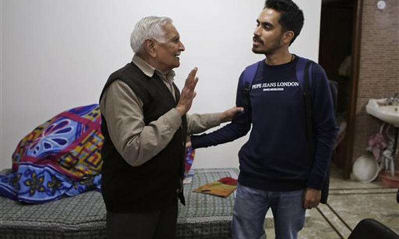 86-year old Desh Raj Kalra talks with Prakhar Joshi, right, at the end of an interview at his residence in New Delhi, India. Joshi has spent the last 15 months crisscrossing the country interviewing about 150 people to record oral histories including the partition of India. Often, this means listening to extremely personal stories of murder, rape and shattered families. —AP