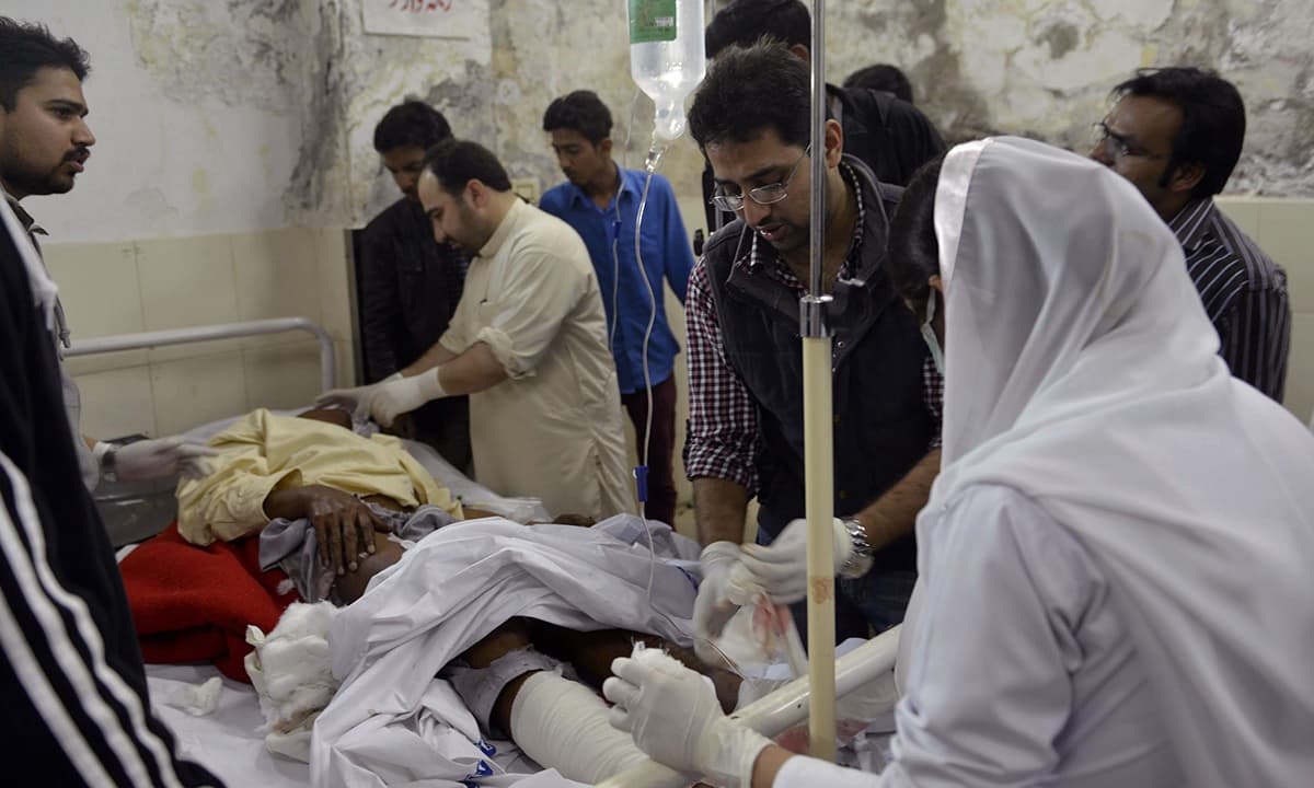 Paramedics treat a victim of a suicide bomb attack on a church in Lahore.— AFP