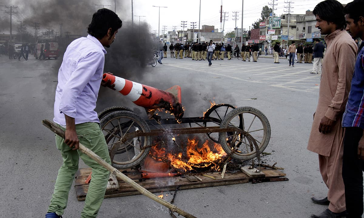 Protesters burn a cart at a road to protest against the suicide bombing attack on two churches.— AP