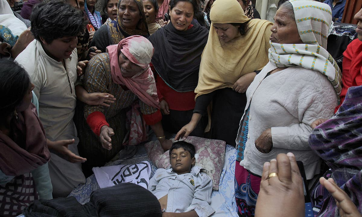 A family mourns over the lifeless body of a boy who was killed in the bombing.— AP
