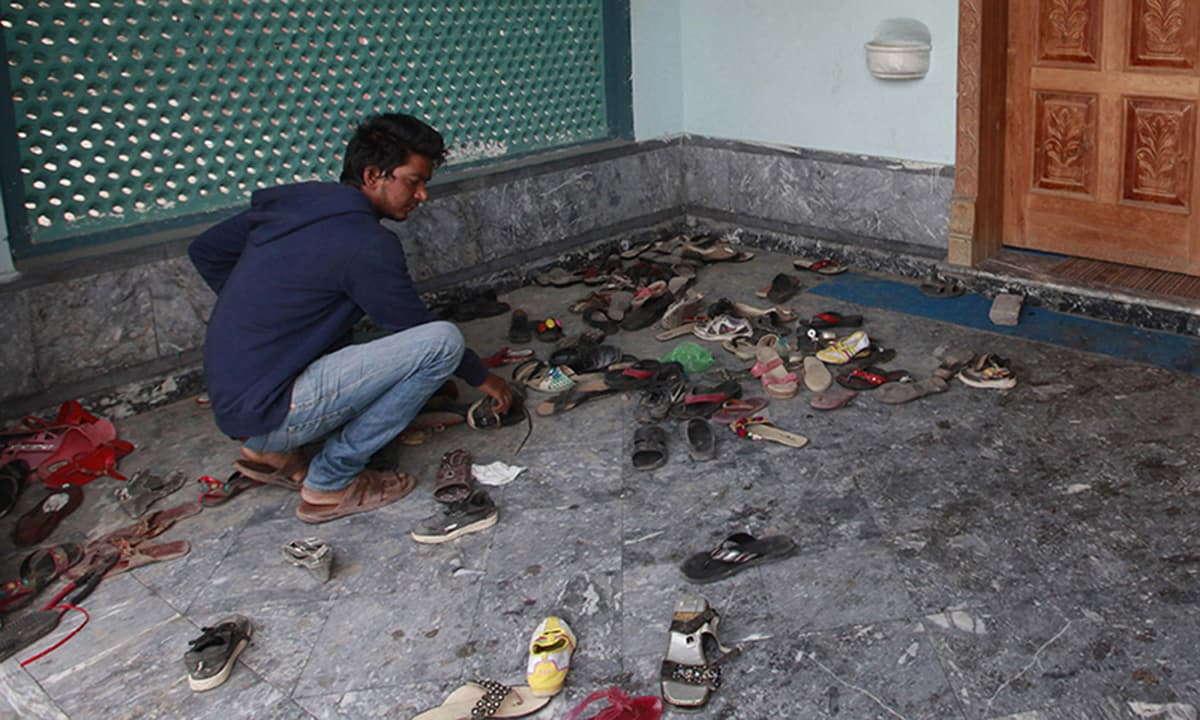 A man checks footwear left behind at a church after a suicide attack in Lahore March 15, 2015. Bombs outside two churches in the Pakistani city of Lahore killed 14 people and wounded nearly 80 during Sunday services, and witnesses said quick action by a security guard prevented many more deaths. A Pakistani Taliban splinter group claimed responsibility.  REUTERS/Mohsin Raza (PAKISTAN - Tags: CIVIL UNREST POLITICS RELIGION)