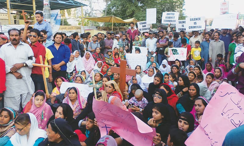 CHRISTIAN men, women and children from across the city gather at the Karachi Press Club to protest against the attacks on churches in Lahore on Sunday.—Photo by writer