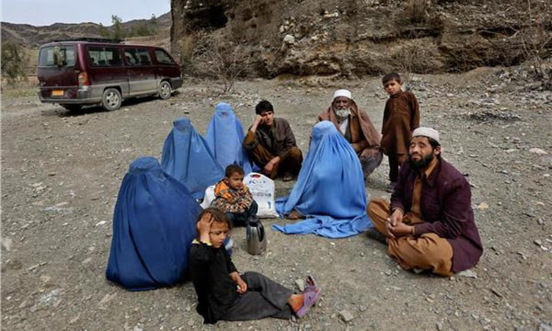 Native Afghan, Nezamuddin, right, sits with his family after returning to Afghanistan through Pakistan's border crossing, Torkham, east of Kabul, Afghanistan.—AP