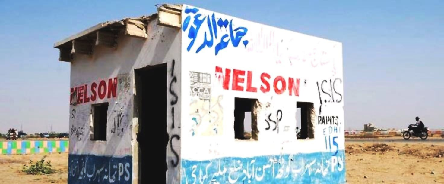 "This picture shows motorists driving past an empty police check post with graffiti which reads as ""ISIS"" along a street on the outskirts of Karachi. —AFP/file"