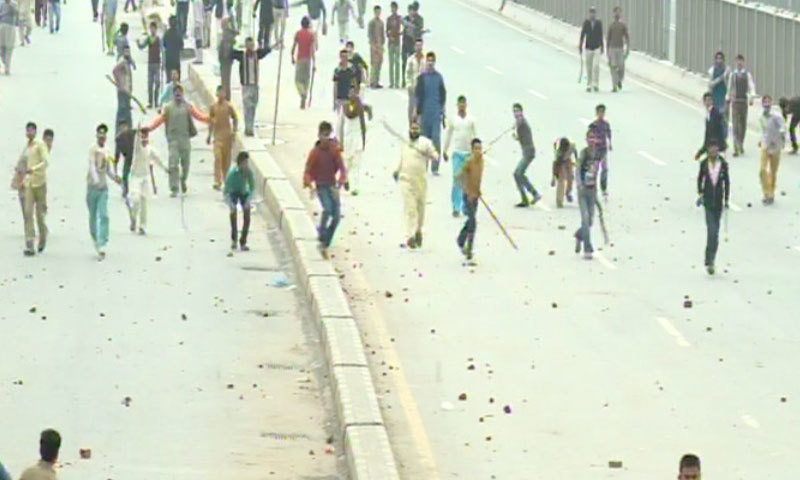 Protesters yield sticks as protest turns violent - DawnNews screen grab