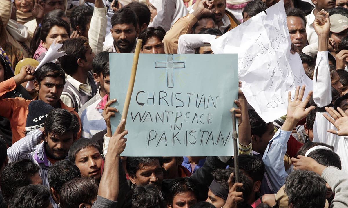 People protest holding placards which asks for peace in Pakistan.— Reuters