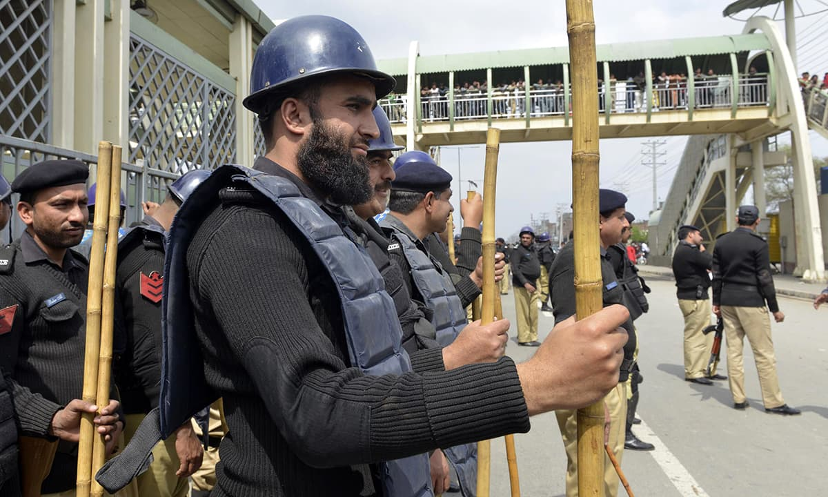 Policemen carry bamboo sticks during a protest by Christians mourners in Lahore.— AFP