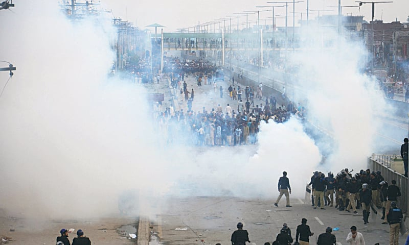 LAHORE: Police use tear gas to disperse Christian protesters here on Monday.—M. Arif / White Star