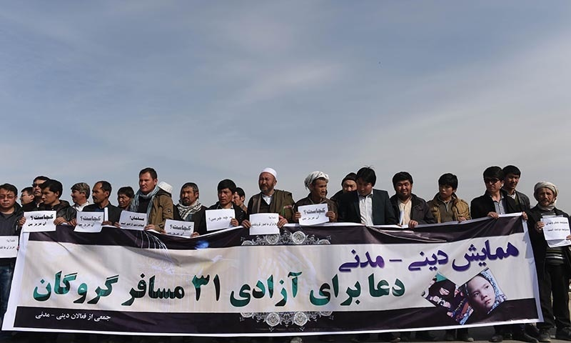 In this photograph taken on March 12, 2015, relatives of 30 Hazaras who were kidnapped hold posters during a gathering in Kabul. — AFP