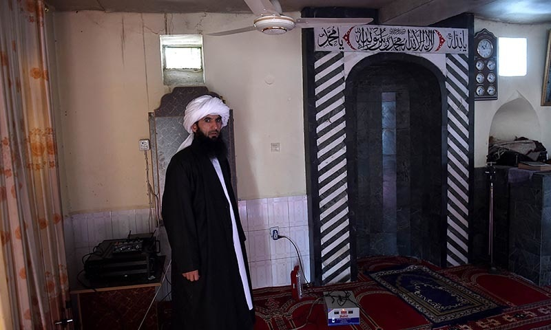 In this photograph taken on March 12, 2015, a Sufi Muslim stands at the place where their leader and his son were shot dead during prayers at the Bahaduria Sufi mosque in Kabul. — AFP