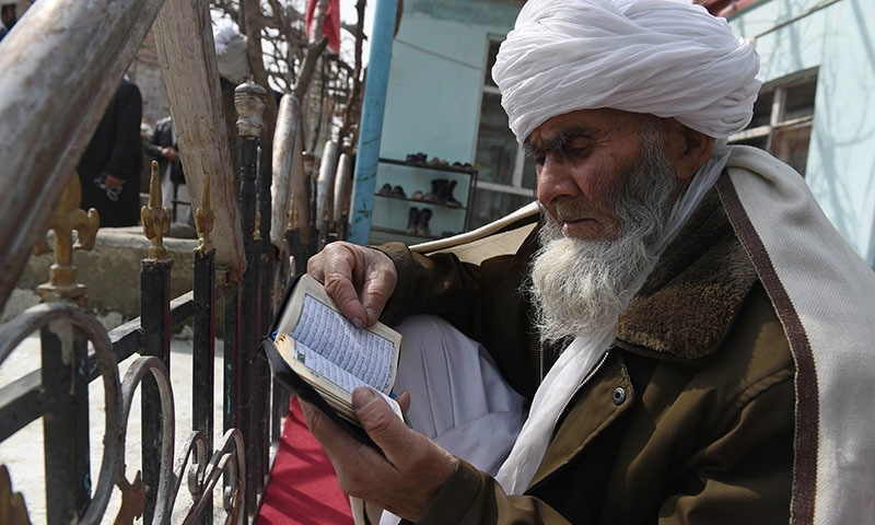 In this photograph taken on March 12, 2015, a Sufi Muslim reads the Koran at the Bahaduria Sufi mosque in Kabul. — AFP