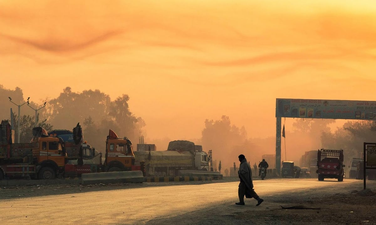The rising sun lights smoke in the air as a man crosses the street near Forward Operating Base Fenty in the Nangarhar province.