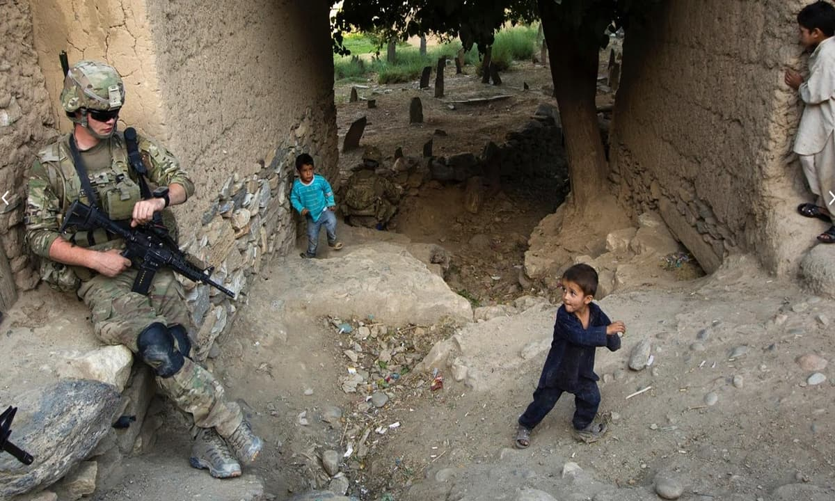 A young Afghan child looks back at Specialist Sean O'Connor during a patrol of the town of Manugay in the Pech River Valley.