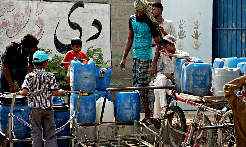 People collect water from a tank in Orangi Town, Sector 11, through a leak in its wall. —Naushad Alam/File