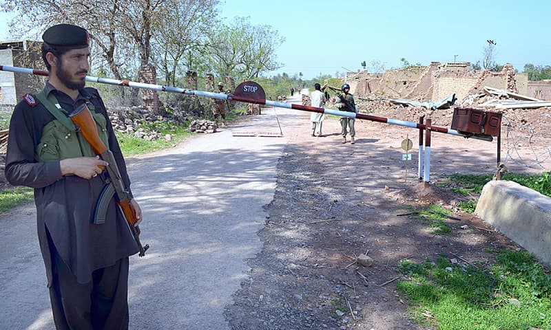 Khasadar force personnel standing alert on a check post in Khyber tribal region's Aka Khel area.— APP