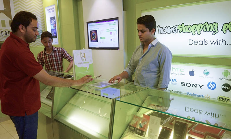 In this photograph taken on March 14, 2015, Shayaan Tahir (R), CEO of Homeshopping.pk, speaks to a customer at his call centre in Karachi.  — AFP