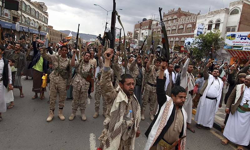 Shia rebels, known as Houthis, hold up their weapons to protest against Saudi-led airstrikes, as they chant slogans during a rally in Sanaa, Yemen. - AP