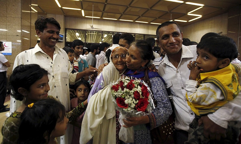 A woman with a bouquet, who was stranded in Yemen, is greeted by her relatives upon  arrival at Jinnah International Airport in Karachi early March 30, 2015.— Reuters