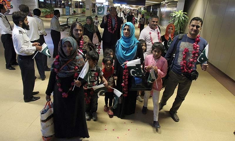 Families, evacuated from Yemen, are greeted by airline staff upon their arrival at Jinnah International Airport in Karachi, Pakistan on Monday, March 30, 2015.— AP