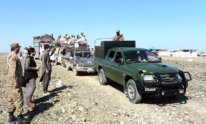 Pakistan Army officials and Political Administration officers receiving IDPs family on returning to their home. — APP