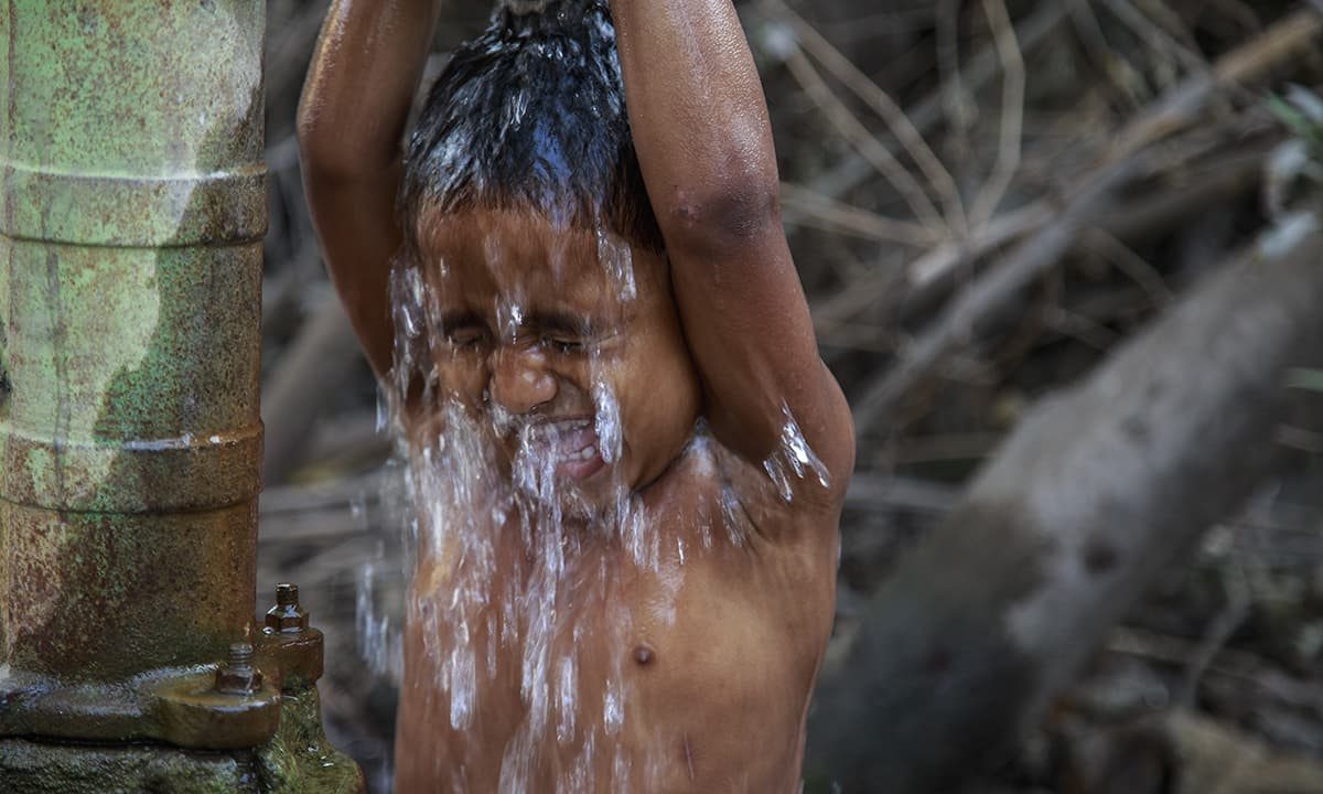 A village boy, taking a shower under a tube well near the Bangladesh border. Absorption of arsenic through the skin is minimal and thus hand-washing, bathing, laundry, etc. do not pose human health risks. — Baba Tamim