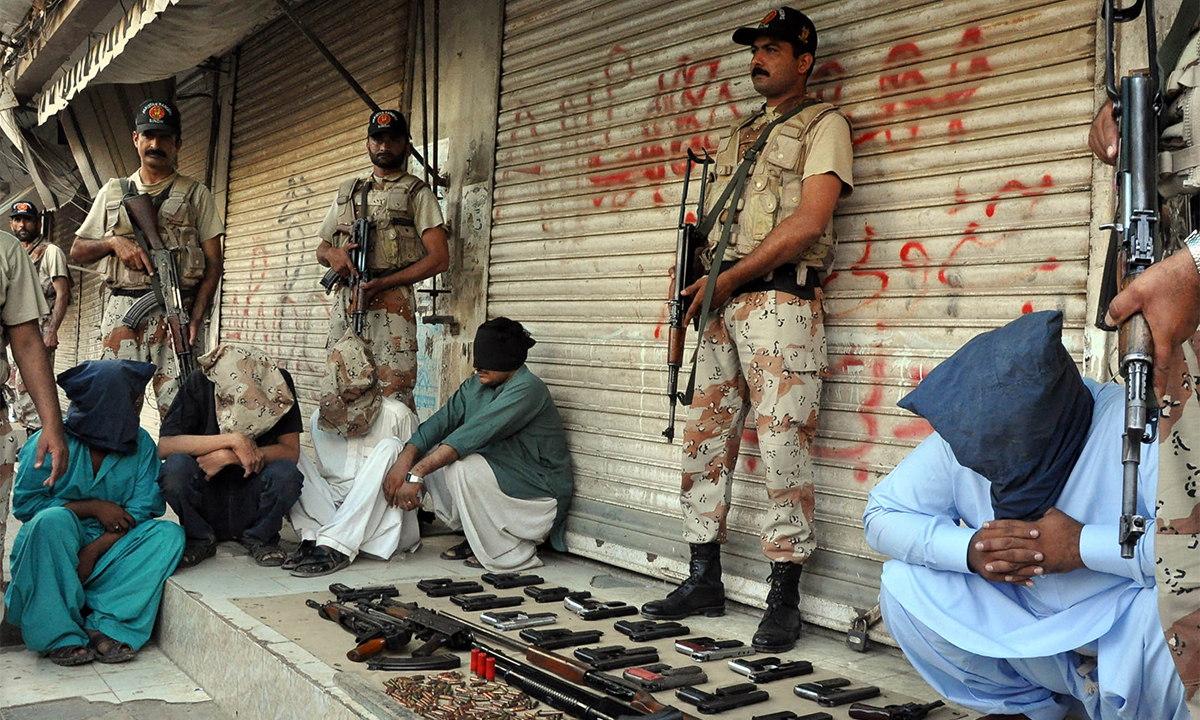 Rangers personnel stand next to suspects and recovered weapons at Baloch Colony.