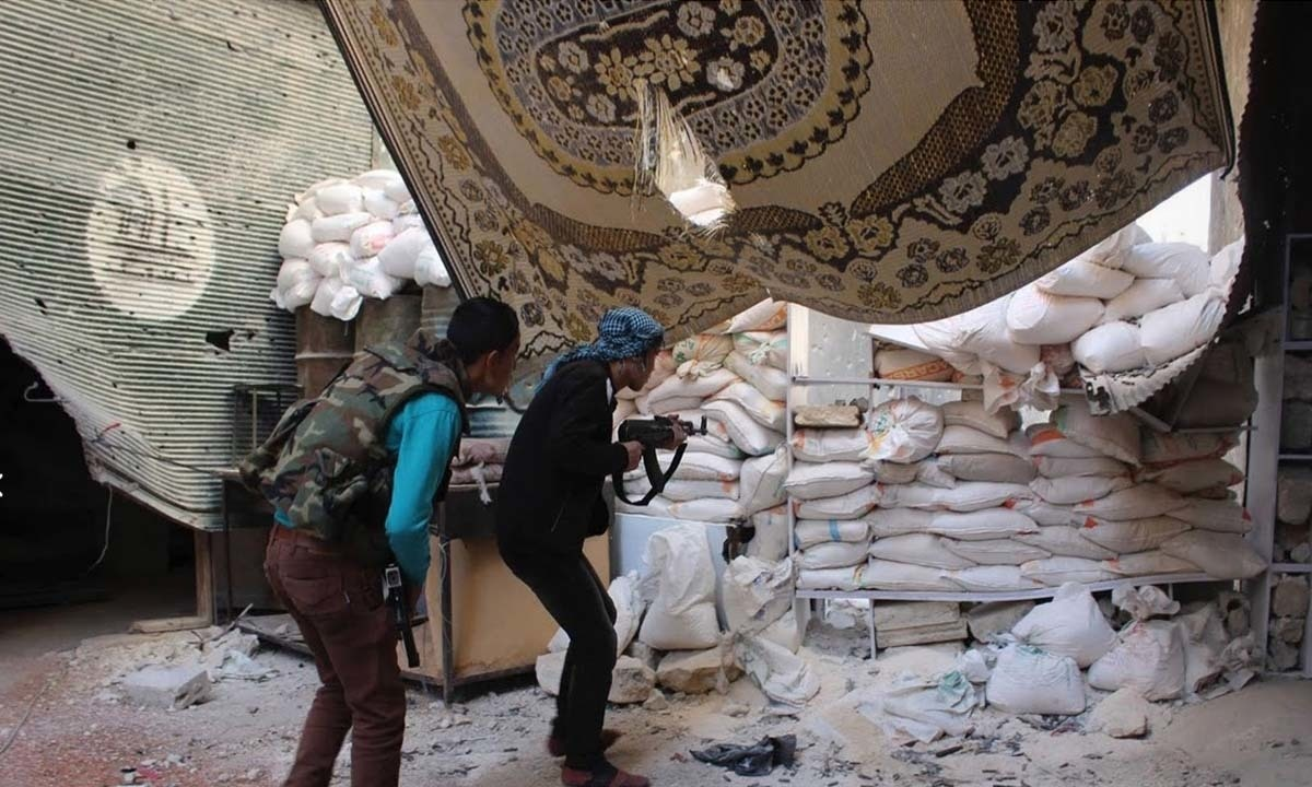 Free Syrian Army fighters take cover behind sandbags in Aleppo's Karm al-Jabal district.