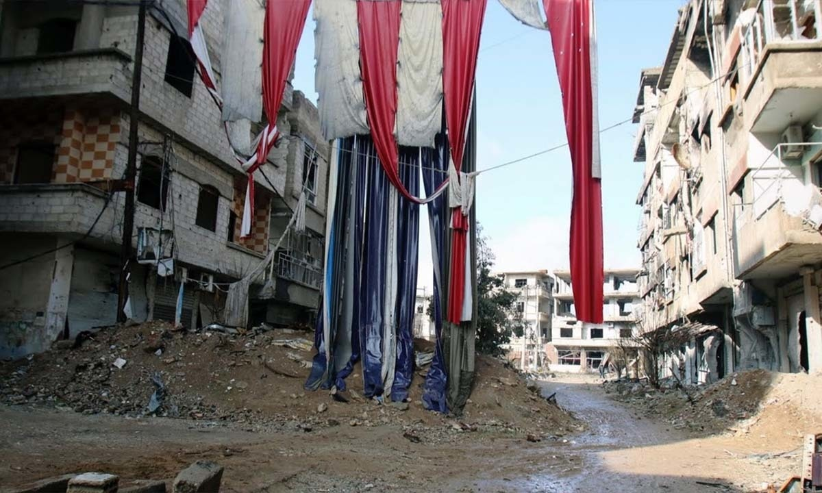 Material is hung to provide cover in the besieged town of Arbeen.