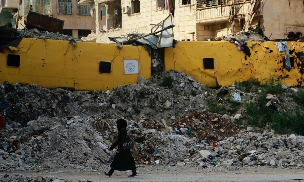 A woman walks past a makeshift barrier built using damaged buses in Aleppo.