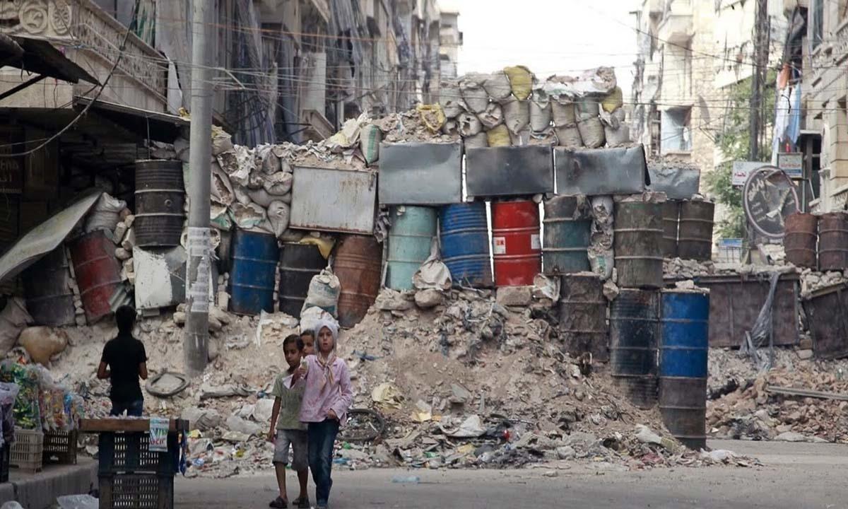 Children walk in front of barrels and sandbags stacked up in a makeshift cover iin the East Al-Ansari neighbourhood.
