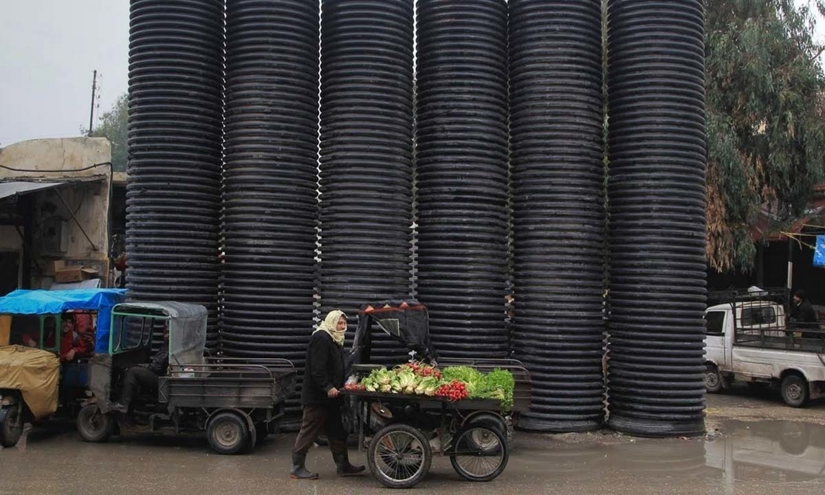 A street vendor pushes a cart loaded with vegetables in front of pipes erected to provide protection from snipers in the old city of Aleppo.