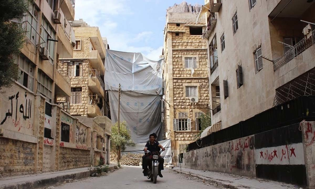 Men ride a motorcycle in front of a cloth placed to cover the street from snipers in Saif al-Dawla district of Aleppo.