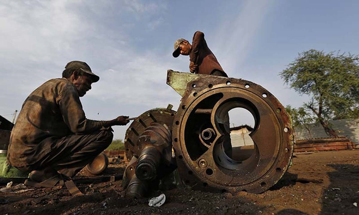 Workers dismantle the engine bearing of a decommissioned ship at the Alang shipyard in the western Indian state of Gujarat.