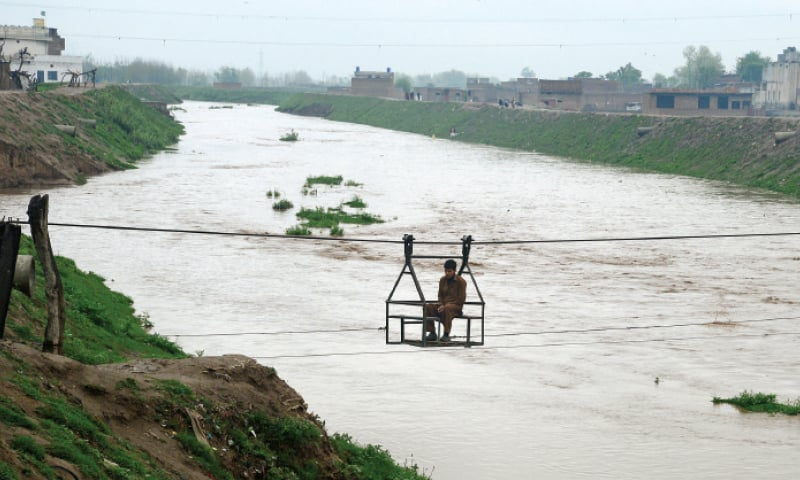 A man uses a chairlift to cross Budhni Nullah, which is in flood due to heavy rain in Peshawar on Wednesday. — Photo by Shahbaz Butt