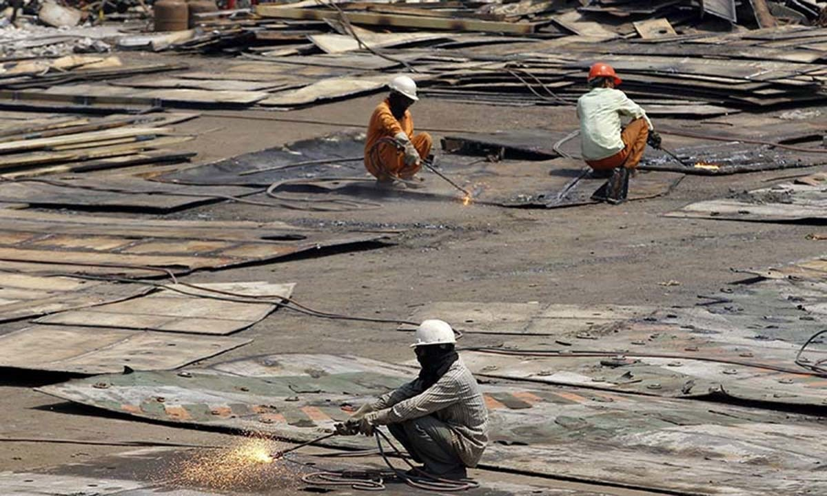 Workers dismantle steel plates of a decommissioned ship at the Alang shipyard.