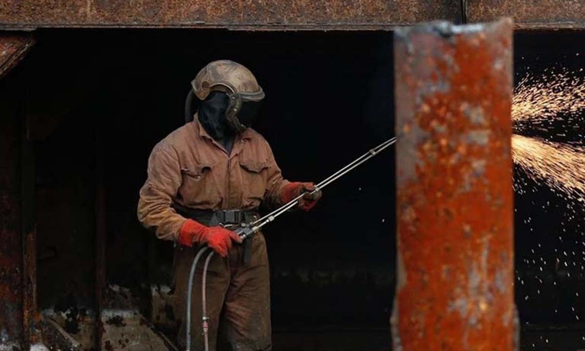 A worker dismantles the hull of a barge at the Galloo plant.