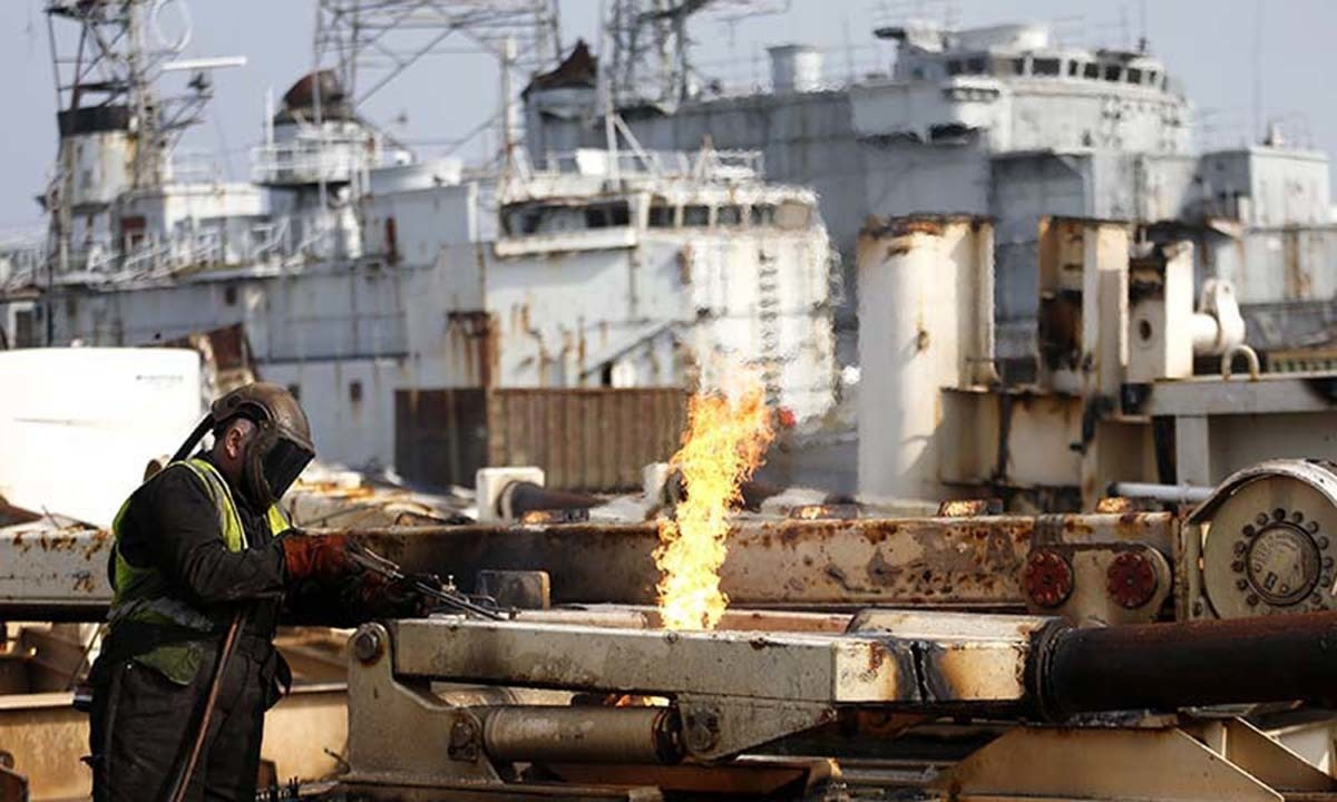 A worker uses a cutting torch on a large block cut from a vessel at the Galloo ship recycling plant in Ghent.