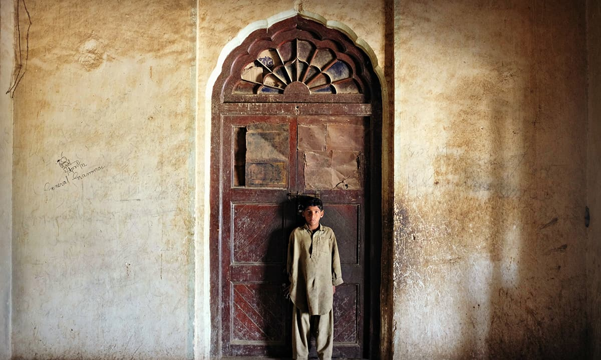 The caretaker's boy stands by a wooden carved door inside the Sheeh Mahal in Khairpur. - Photo by Farooq Soomro