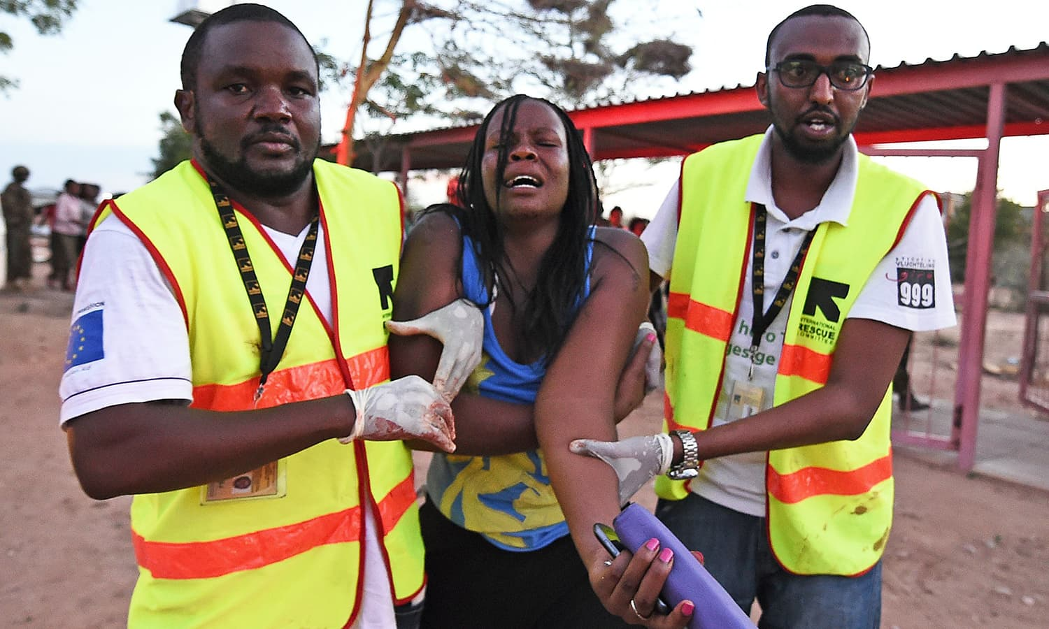 Paramedics help a woman who was injured during an attack by Somalia's Al-Qaeda-linked Shebab gunmen on the Moi University campus in Garissa. -AFP