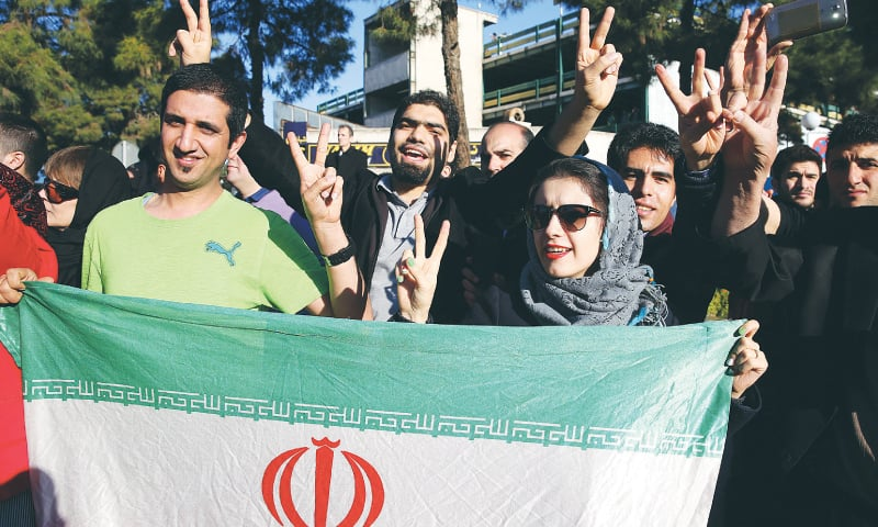 TEHRAN: Jubilant Iranians flash the victory sign as they hold their country's flag while waiting at the Mehrabad airport for arrival of Foreign Minister Mohammad Javad Zarif from Lausanne, Switzerland, on Friday.—AP